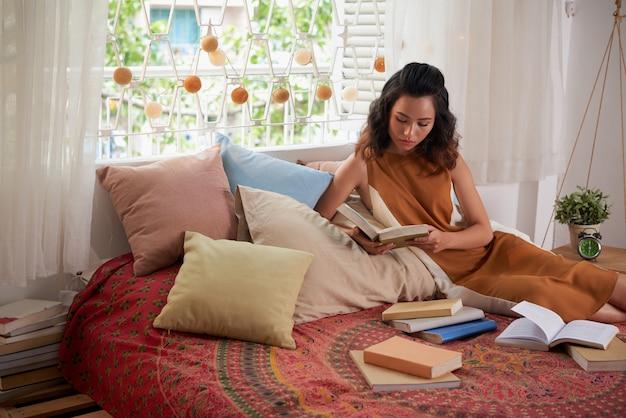 Retrato de menina adolescente lendo livros de texto na cama dela