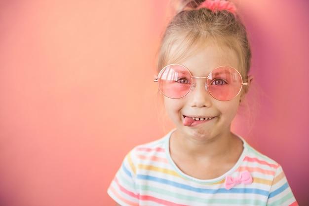 Retrato de menina adolescente louca mostra a língua em óculos de sol rosa