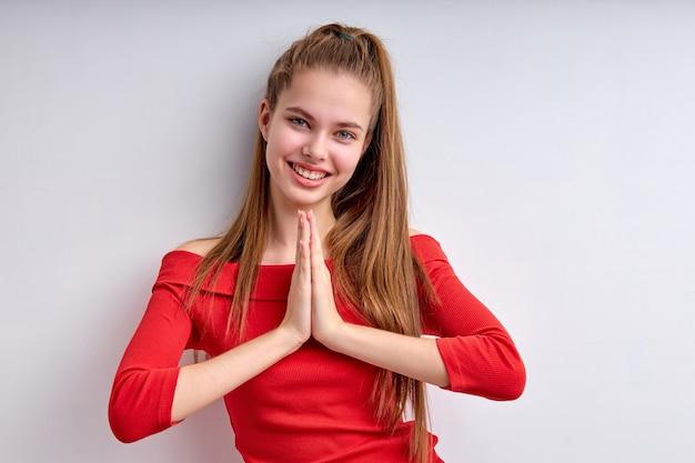 Retrato de menina adolescente positiva, mantendo as mãos juntas, olhando para a câmera amiling olhando feliz dreami ...