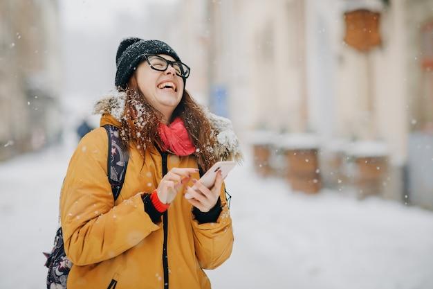 Retrato, de, menina adolescente, segurando telefone móvel, exterior, em, inverno