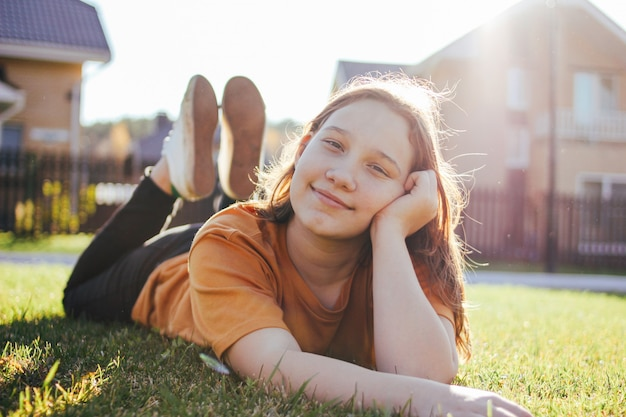 Retrato de menina adolescente sorridente, deitado na grama verde ensolarada da vila de chalé em fundo