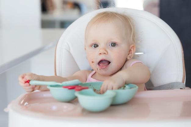 Retrato de menina adorável bebê brincando com comida