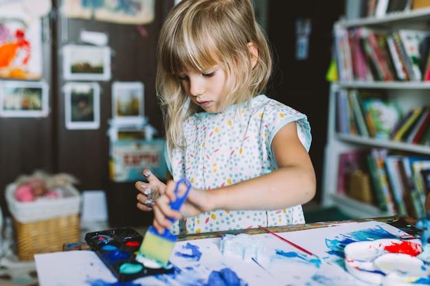 Retrato de menina adorável bebê pintando em casa