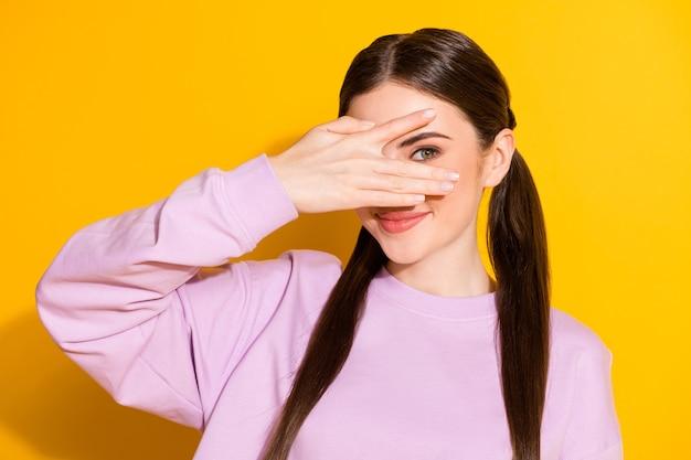 Retrato de menina adorável bonita positiva escondendo o rosto com a mão