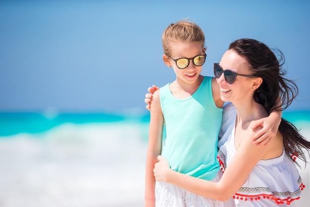 Retrato de menina adorável e jovem mãe na praia tropical