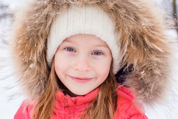 Retrato de menina adorável na neve dia ensolarado de inverno