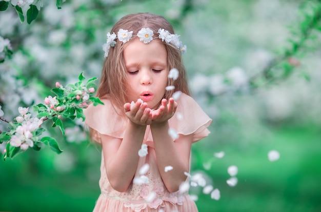 Retrato de menina adorável no jardim de cerejeira desabrocham ao ar livre