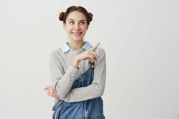 Retrato de menina adulta muito positivo com pães duplos, apontando o dedo. jovem arquiteto feminino com dignidade, demonstrando seu trabalho na parede branca. copie o espaço