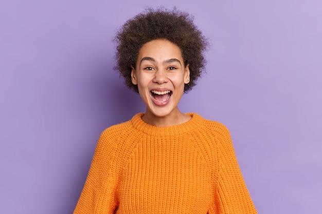 Retrato de menina afro-americana positiva ri alegremente mantém a boca aberta tem dentes brancos ouve notícias engraçadas vestida com suéter de malha laranja.