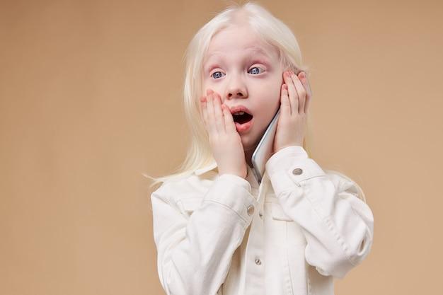 Retrato de menina albina surpresa com telefone