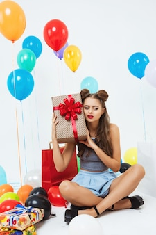 Retrato de menina alegre, adivinhando o que está na caixa