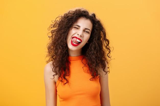 Retrato de menina alegre, brincalhão e elegante caucasiana com cabelo encaracolado e batom vermelho piscando showi.