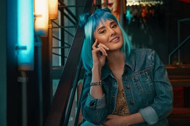 Retrato de menina alegre com cabelo azul elegante e rosto bonito