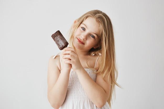 Retrato de menina alegre com olhos azuis e cabelos claros, desfrutando de um sorvete com chocolate permanece em seu rosto. infância feliz e despreocupada