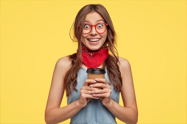 Retrato de menina alegre e alegre usa bandana vermelha, vestido jeans e óculos, segurando café para viagem em copo descartável de papel