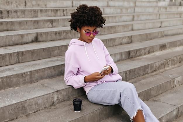 Retrato de menina alegre e encaracolada em calças jeans, óculos de sol rosa e capuz roxo segurando o telefone e sentada na escada ao ar livre
