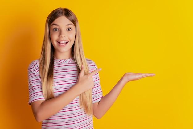 Retrato de menina alegre espantada segurando anúncio de espaço vazio com a palma da mão apontando dedo sobre fundo amarelo