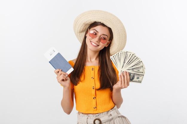 Retrato de menina alegre, feliz e rindo com chapéu na cabeça, tendo dinheiro fã e passaporte com bilhetes nas mãos, isolado no branco