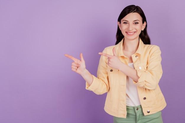 Retrato de menina alegre indica os dedos indicadores afastando o espaço vazio no fundo violeta
