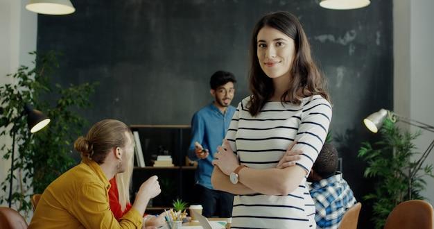 Retrato de menina alegre muito jovem, virando o rosto para a câmera e sorrindo. equipe de startuppers em segundo plano.