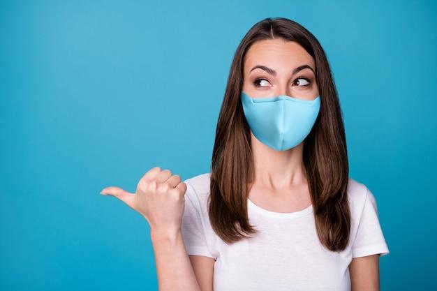 Retrato de menina alegre positiva apontar dedo polegar copyspace demonstrar publicidade secreta promoção usar roupas de boa aparência máscara médica isolada sobre fundo de cor azul