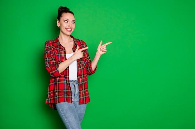 Retrato de menina alegre positiva apontar o dedo indicador copyspace recomendar sugerir seleção de anúncios promoção usar jeans isolado sobre fundo de cor brilhante