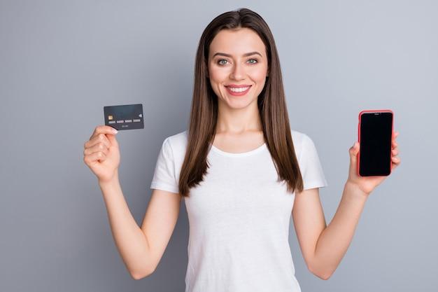 Retrato de menina alegre positiva segurando smartphone pagamento com cartão de crédito