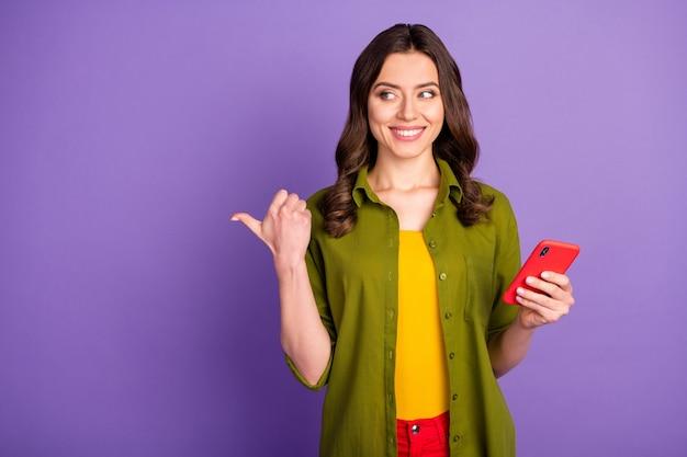 Retrato de menina alegre positiva usando smartphone indicar rede social anúncio de desconto promoção ponto polegar dedo copyspace vestir estilo roupa elegante isolado sobre fundo de cor roxa