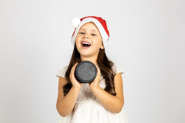 Retrato de menina alegre rindo com chapéu de papai noel segurando alto-falante de música inteligente ou estação isolada ...