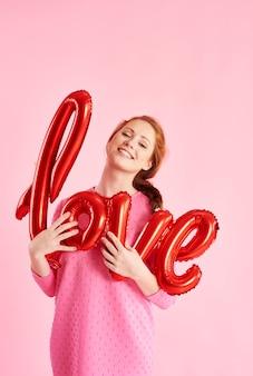 Retrato de menina alegre segurando um balão em estúdio.
