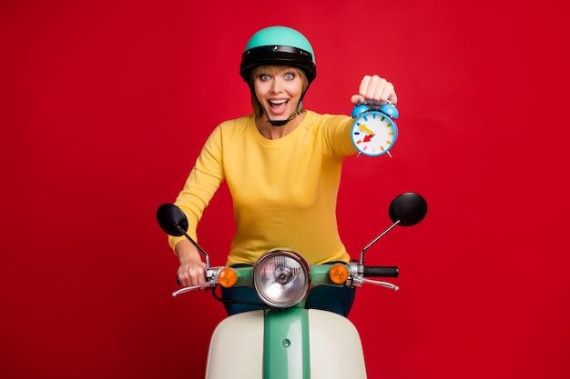 Retrato de menina animada andando de moto em alta velocidade segurando o relógio