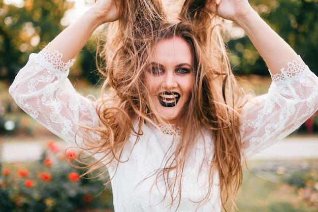 Retrato de menina animada com maquiagem gótica, esticando seus longos cabelos com expressão facial.