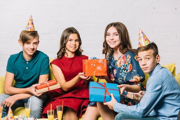Retrato, de, menina aniversário, com, seu, amigos, segurando apresenta, em, mão