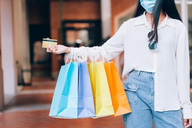 Retrato de menina asiática animado linda garota usando máscara protetora feliz, sorrindo com segurando o cartão de crédito e sacolas de compras, desfrutando em compras de expressão relaxada, conceito de estilo de vida.