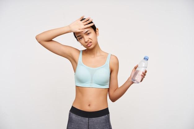 Retrato de menina asiática cansada e desportiva, com cabelo comprido escuro. vestindo roupas esportivas e segurando uma garrafa de água. parecendo exausto, com sede. assistindo a câmera isolada sobre fundo branco