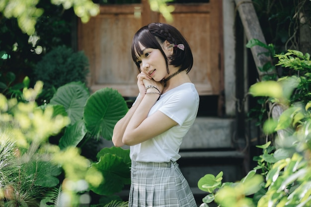 Retrato de menina asiática com camisa branca e saia, olhando no estilo de filme vintage de natureza ao ar livre