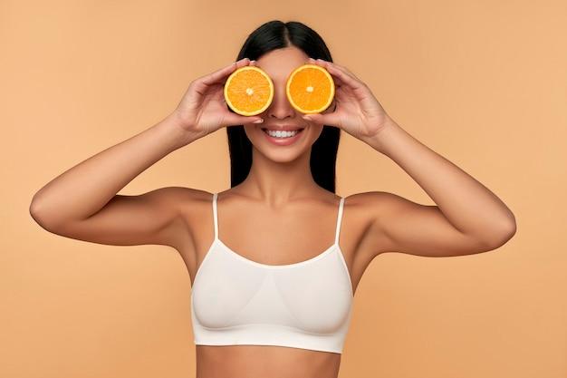 Retrato de menina asiática com rosto limpo e brilhante segurando metades de laranja em cueca branca isolada em bege