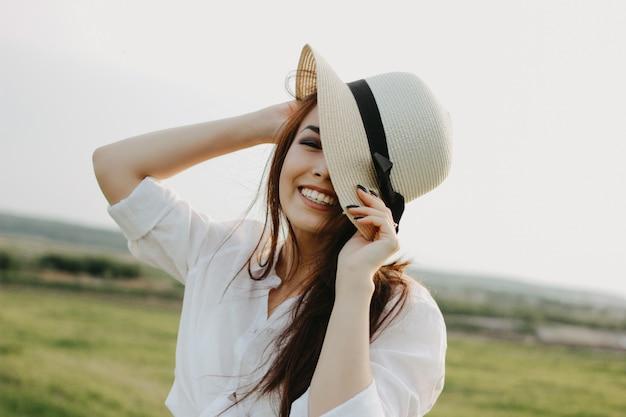 Retrato de menina asiática de cabelo comprido despreocupado bonito em roupas brancas e chapéu de palha aprecia a vida no campo da natureza