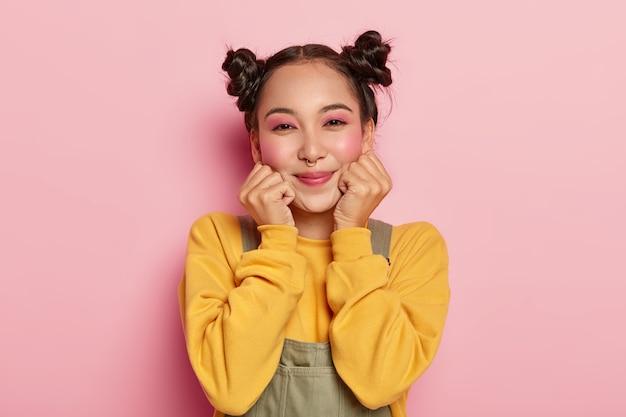 Retrato de menina asiática feliz com maquiagem pinup, cabelo escuro penteado em dois coques, piercing no nariz, usa moletom amarelo casual e macacão