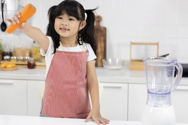 Retrato de menina asiática feliz com uma cenoura