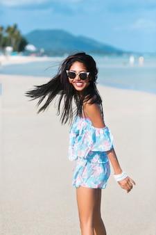 Retrato de menina asiática tailandesa com óculos escuros e vestido florido se divertindo em uma praia tropical