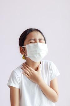 Retrato de menina asiática tocando seu pescoço com dor de garganta
