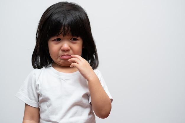 Retrato de menina asiática triste com raiva e choro em fundo branco isolado a emoção de uma criança