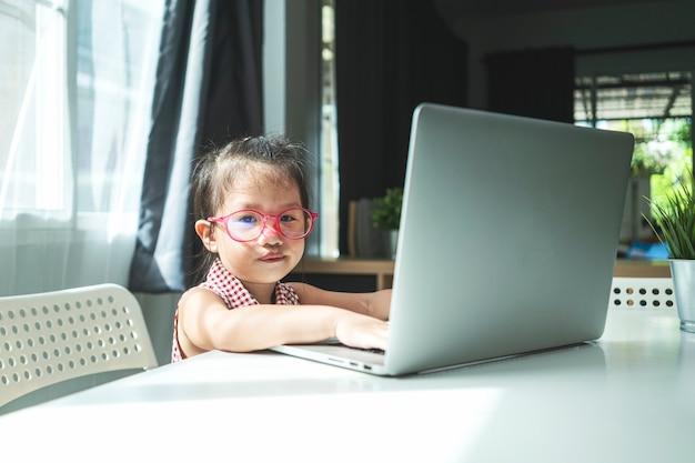 Retrato de menina asiática usando computador portátil para aplicação online, estudando em casa. ensino doméstico, aprendizagem online ou conceito de educação