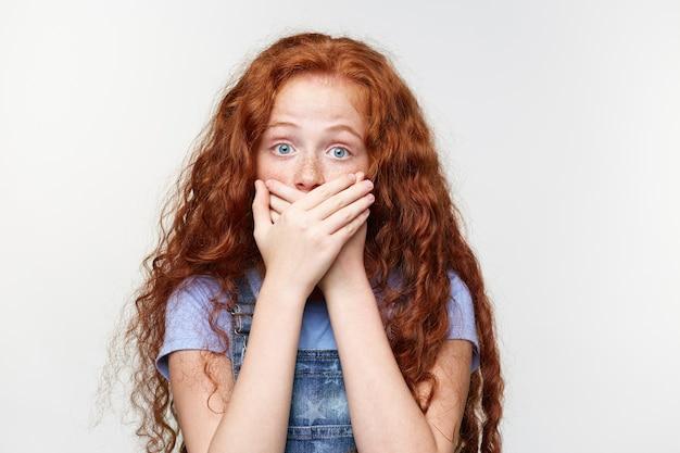 Retrato de menina assustada de sardas fofas com cabelos ruivos, ouve uma terrível tontura, boca coberta com as palmas das mãos, fica em pé sobre uma parede branca com os olhos bem abertos e expressão assustada.