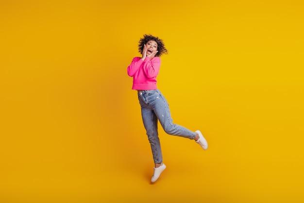 Retrato de menina ativa e positiva pulando, se divertindo no fim de semana livre, isolado no fundo amarelo