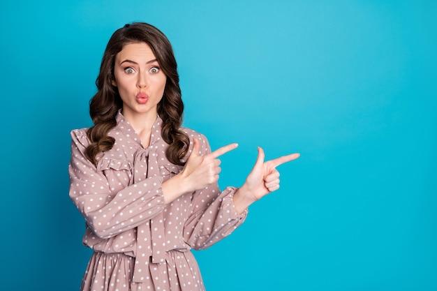Retrato de menina atônita apontar o dedo indicador copyspace indica promoção de anúncios incrível demonstrar maneira direta vestir camisa pontilhada isolada sobre fundo de cor azul