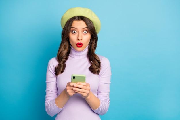 Retrato de menina atônita, usando o celular, lendo informações da rede social, impressionado, estupor, vestindo jumper de roupa de cor lilás isolado sobre parede de cor azul