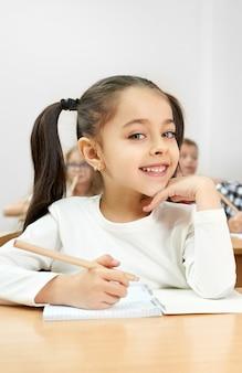 Retrato de menina atraente, olhando para a câmera na escola