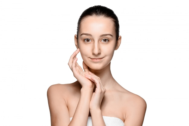 Retrato de menina bonita, acariciando o rosto com uma pele saudável